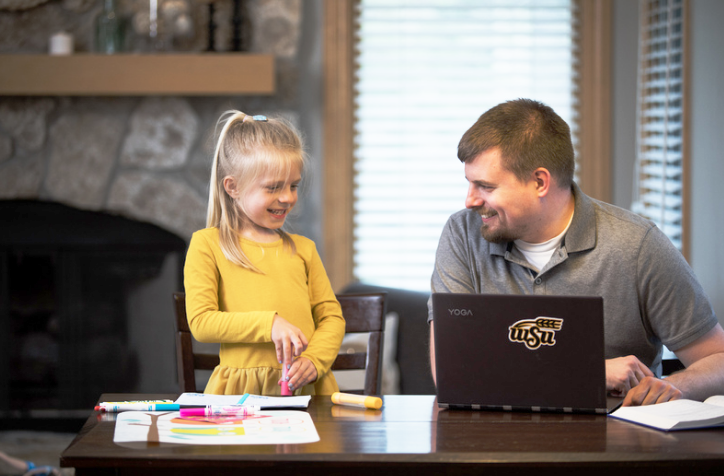 Father on laptop and smiling at daughter