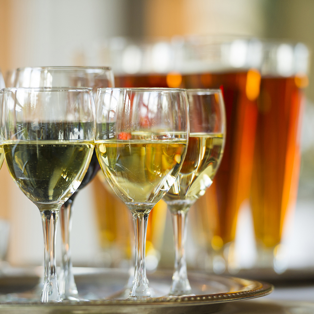 Beer and wine glasses on serving trays at an event