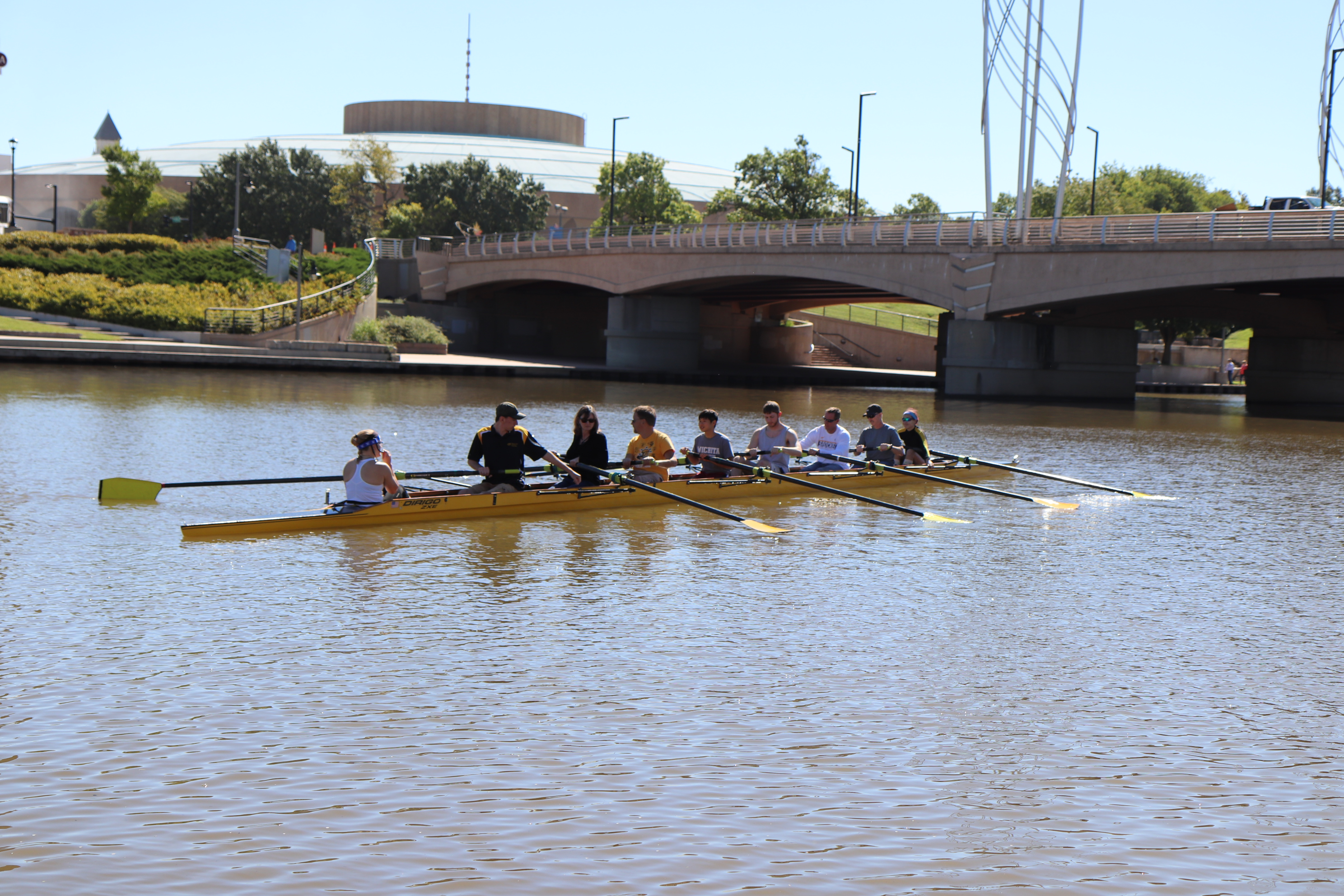 A family fun row boat on the water, filled with a mixture of rowers and parents.