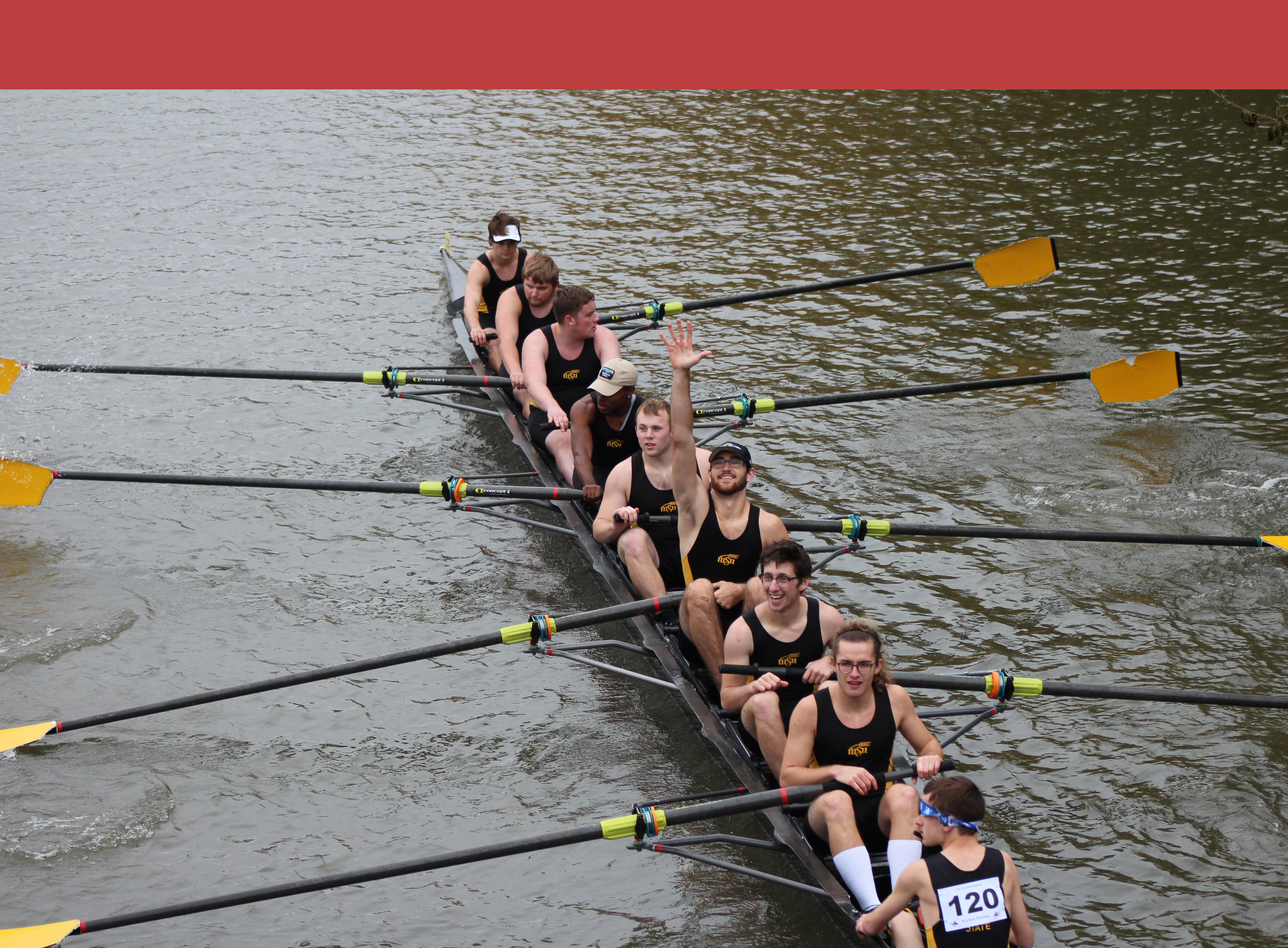 Men's novice 8. One of the men in the middle of the boat has his hand upraised and is smiling at the camera. All the rest are focused on rowing like good rowers.