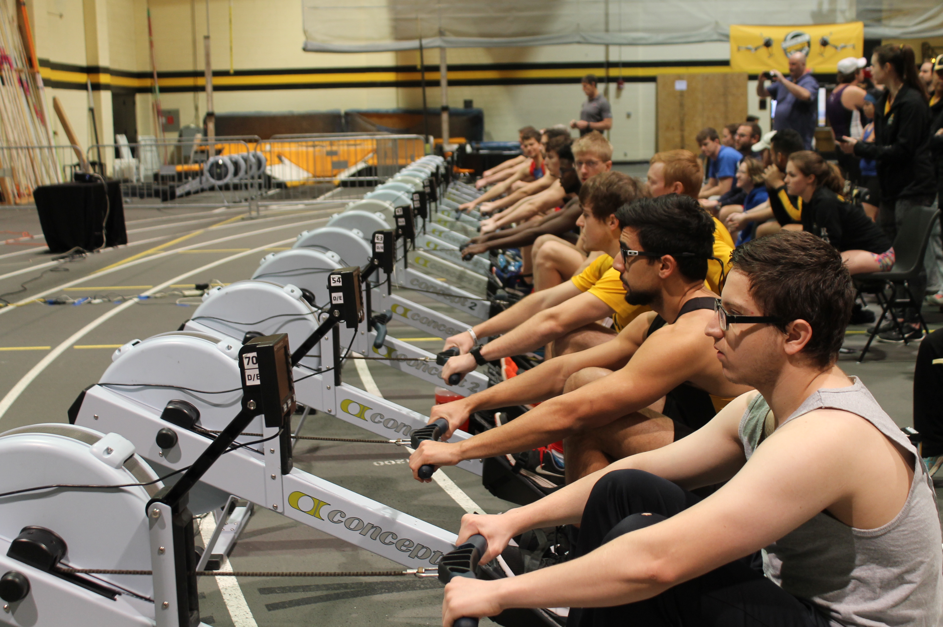 Looking down the row of ergometers at shocker sprints. its a men's event, and everyone is holding, waiting for the race to begin
