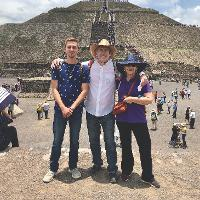 Three people standing with the Teotihuacan pyramid in the background.