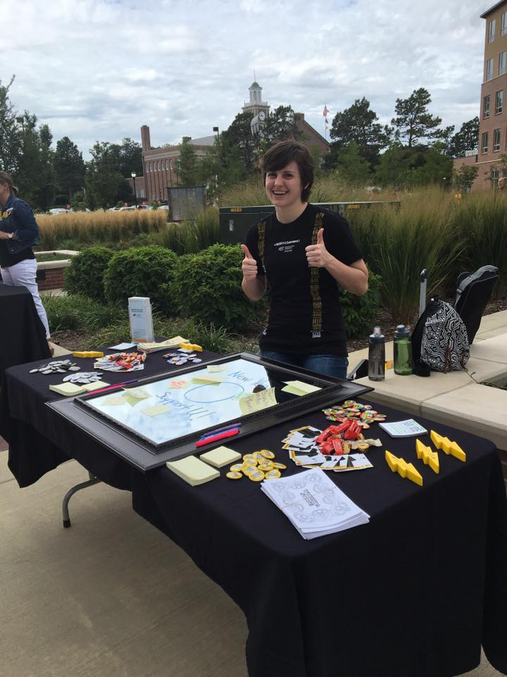 Staff member giving two thumbs up at a tabling event.
