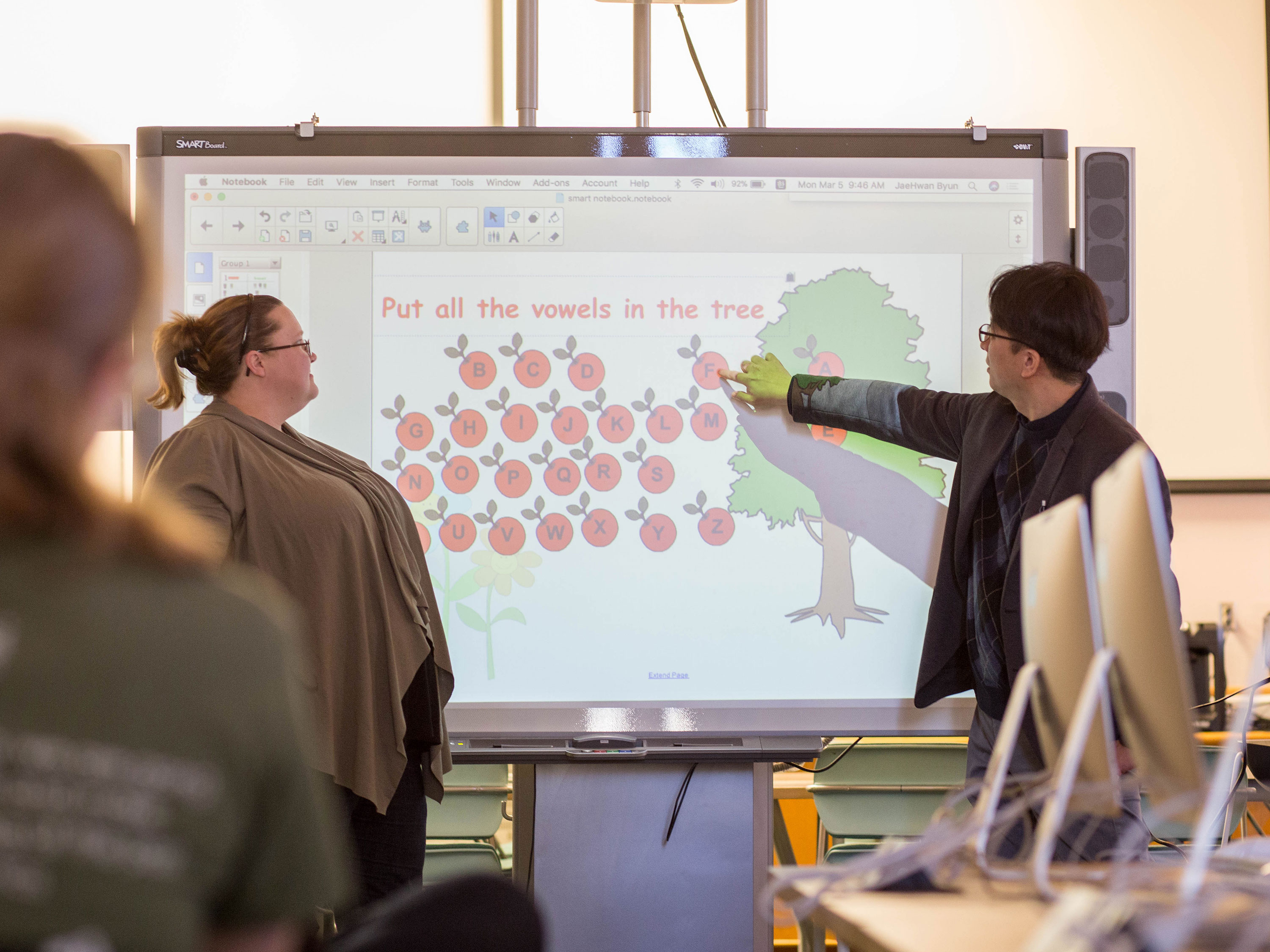 An instructor and student work collaboratively on a digital whiteboard in a College of Applied Learning classroom