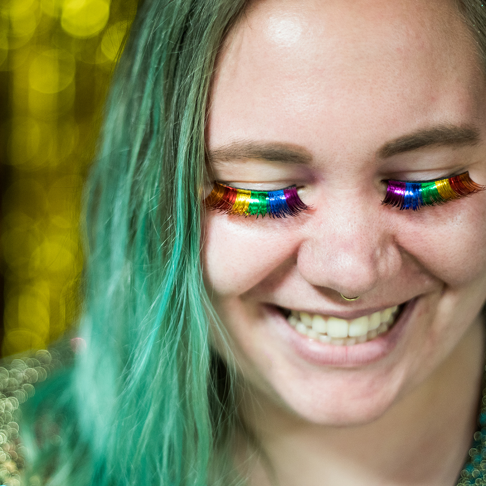 A student wearing rainbow-colored lashes at the annual Pride Prom.