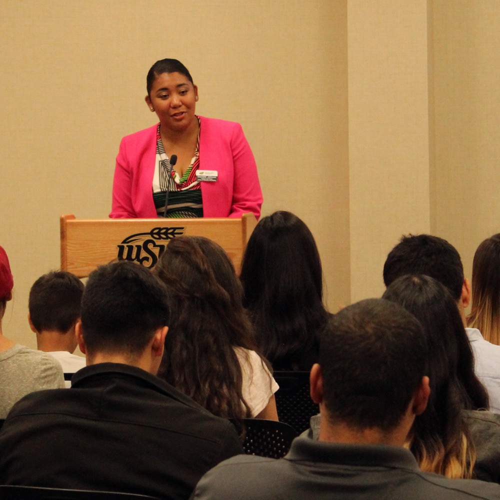 An employee speaking at the podium to a group at a diversity training.