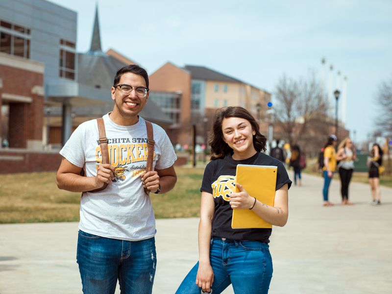 Two students smiling on campus.