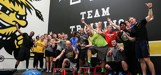 The team of Shocker Fit trainers poses in the F45 room. There is about 30 of them doing fun, outrageous, or aggressive poses.