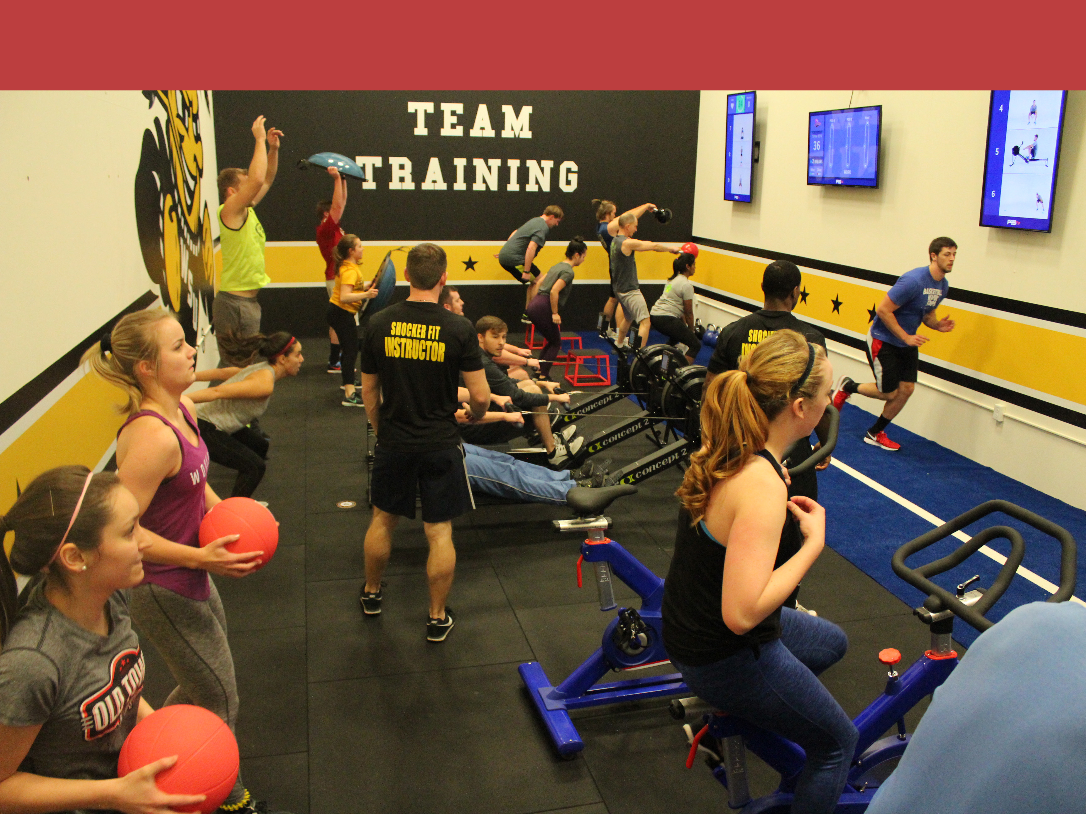 Group of people participating in F45 class. There are lots of excersizes going on, including bliking, medicine ball, kettleball, running, and rowing machine. the instructor is walking through this mess.