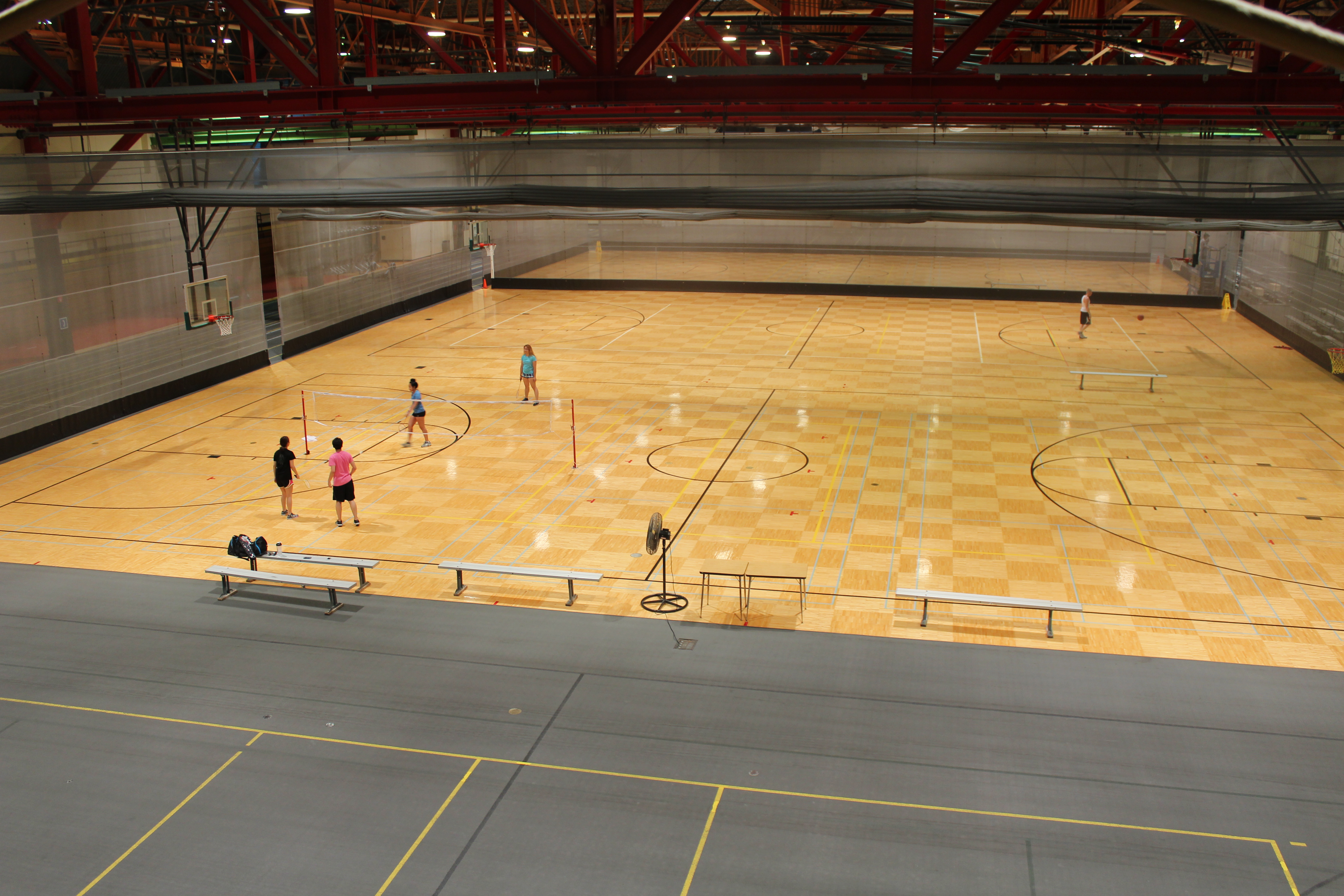 view from a high place of people playing badminton on the gym floor
