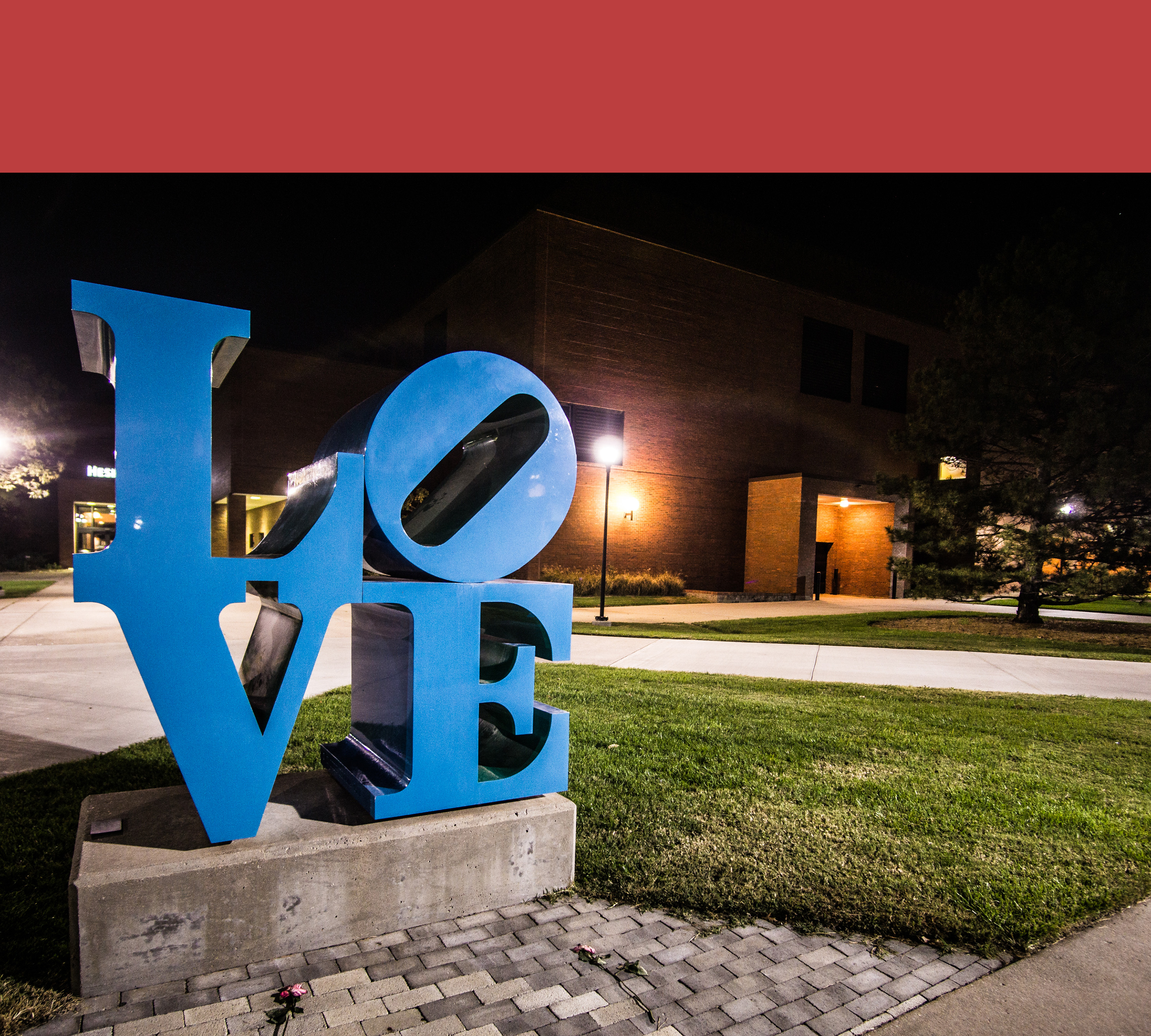 shot of the LOVE artwork sculpture outside of the Heskett Center. it is dark and the lightpoles are lit up.