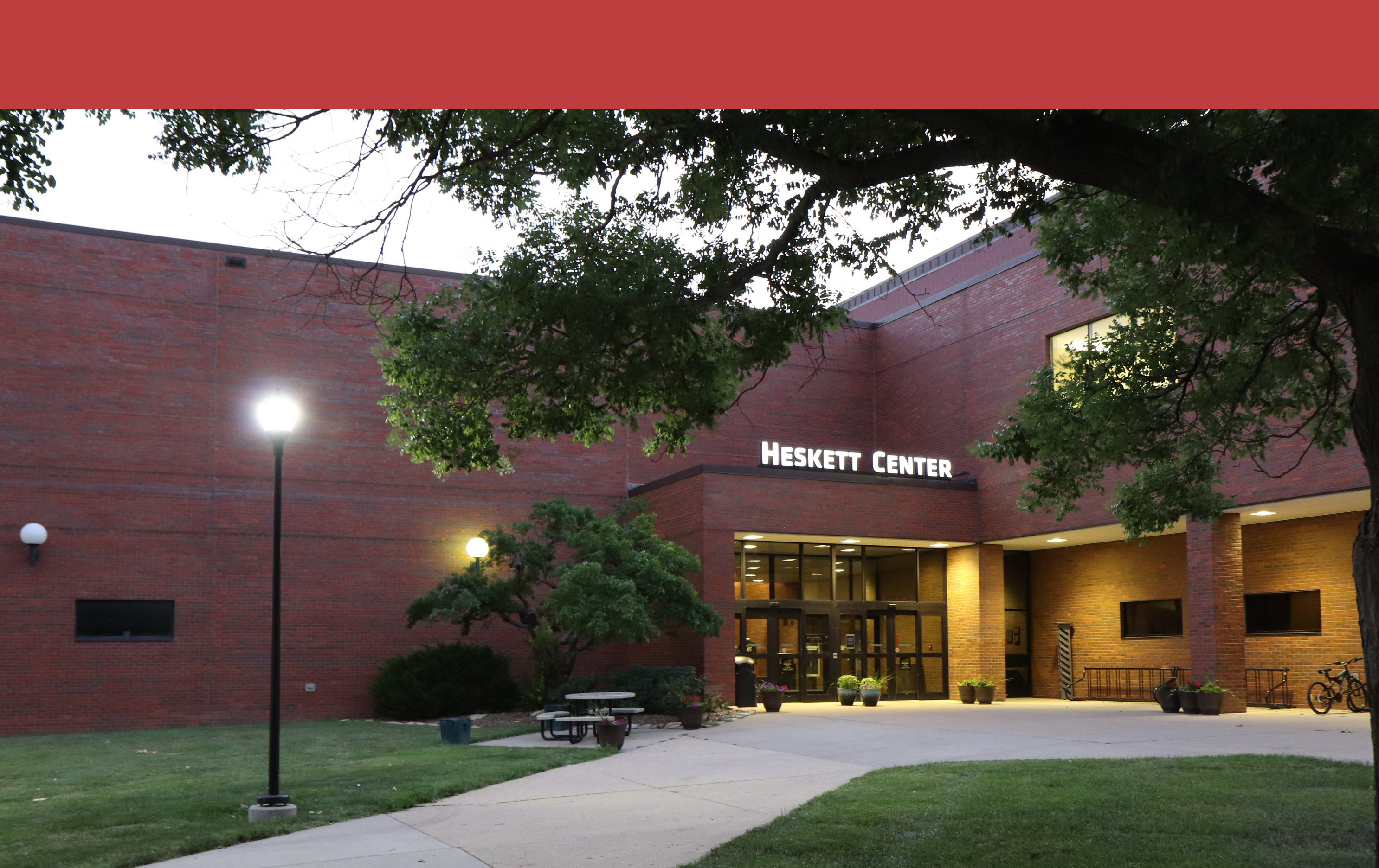 View of the Heskett Center from the outside. The sign above the door is lit up, as is the lamp post in the left of the image.