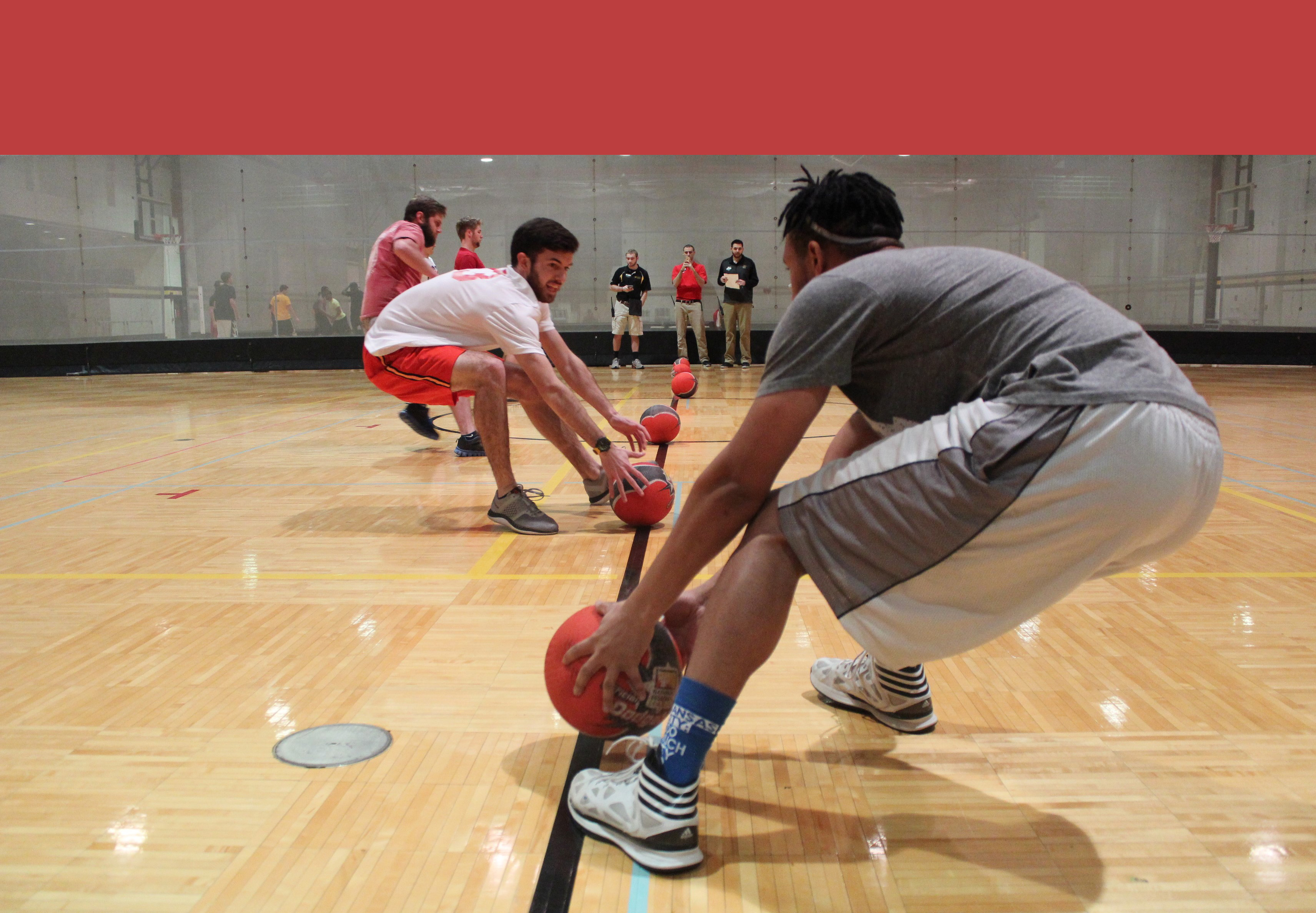 Beginning of a dodgeball match; two boys grab balls on the centerline, poised to spring away back onto their side, away from the opponent.