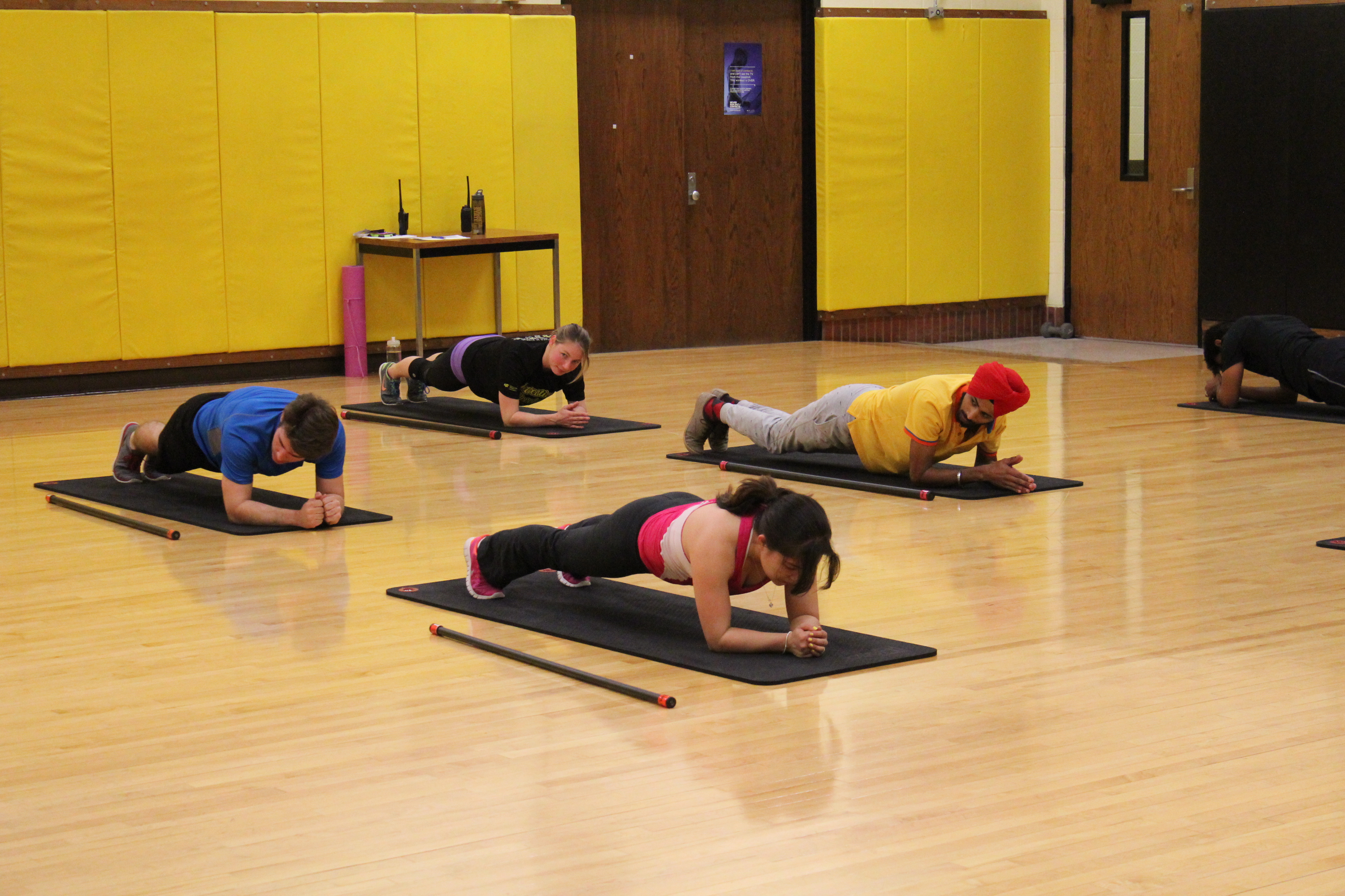 four people on the floor on yoga mats. They are holding planks on their elbows.