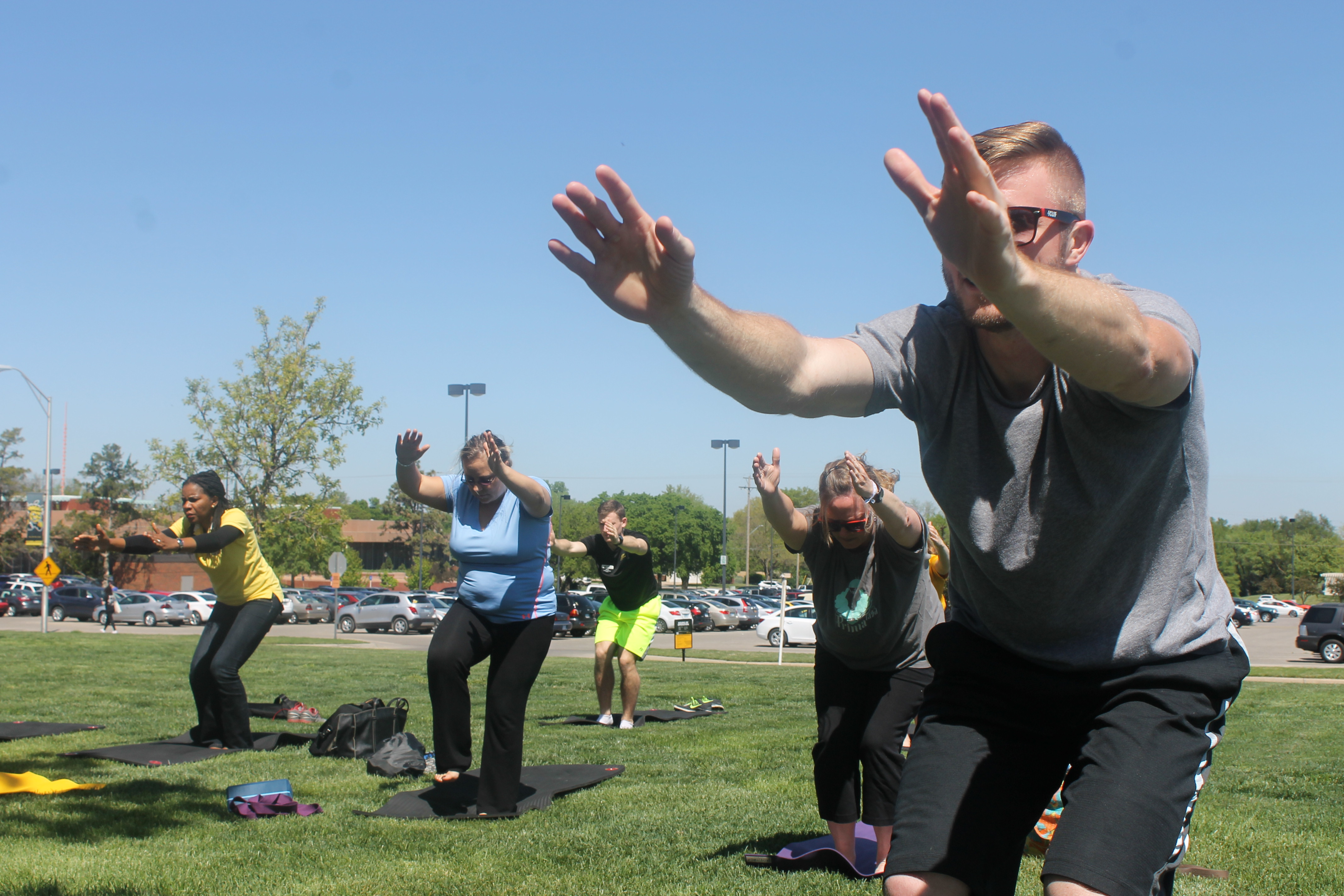 group of people doing outdoor yoga. Front most is a man in sunglasses reaching forward.