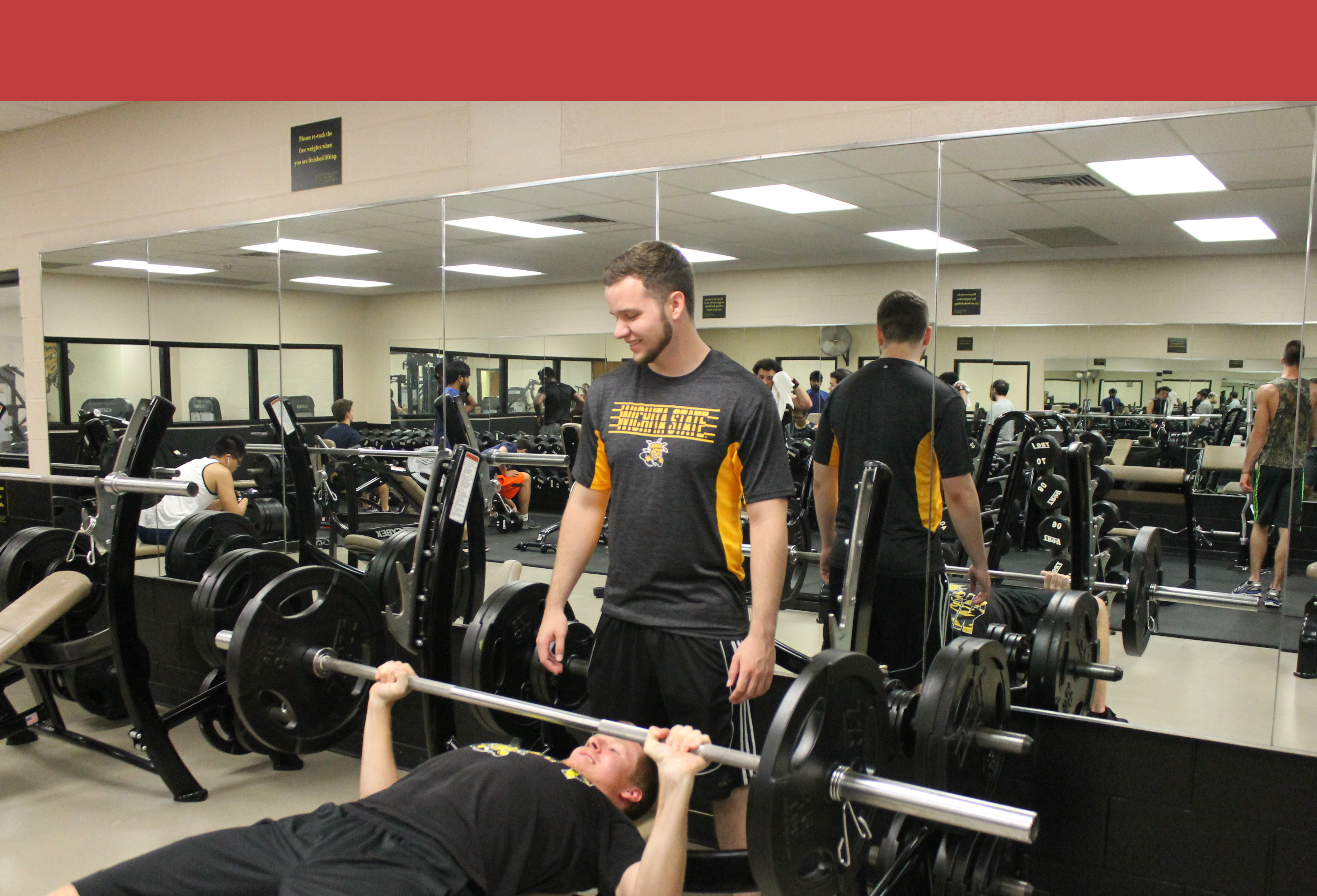 Man doing bench press in the weight room, another man, smiling, is spotting him