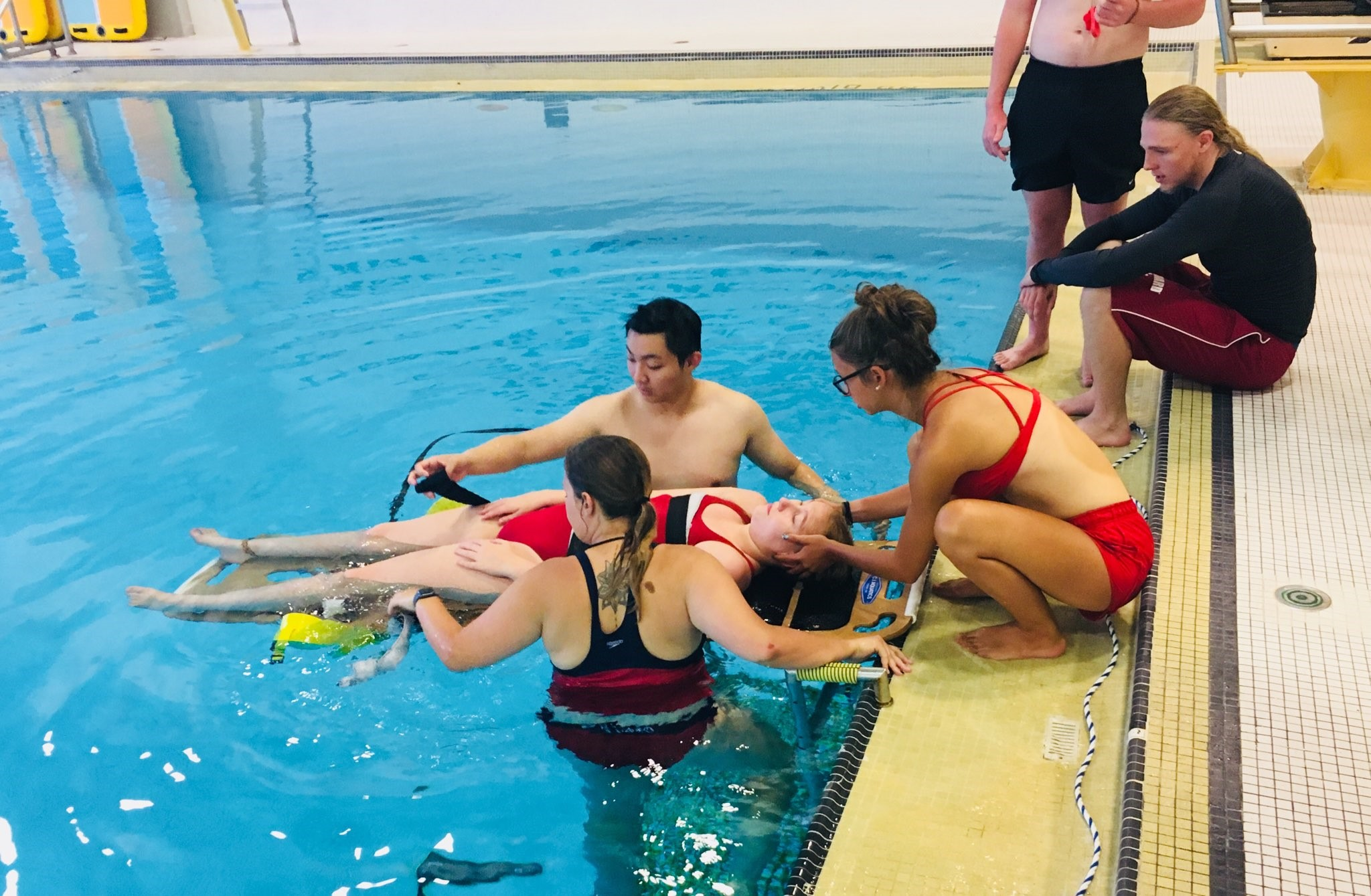 Lifeguards performing practice pool rescue