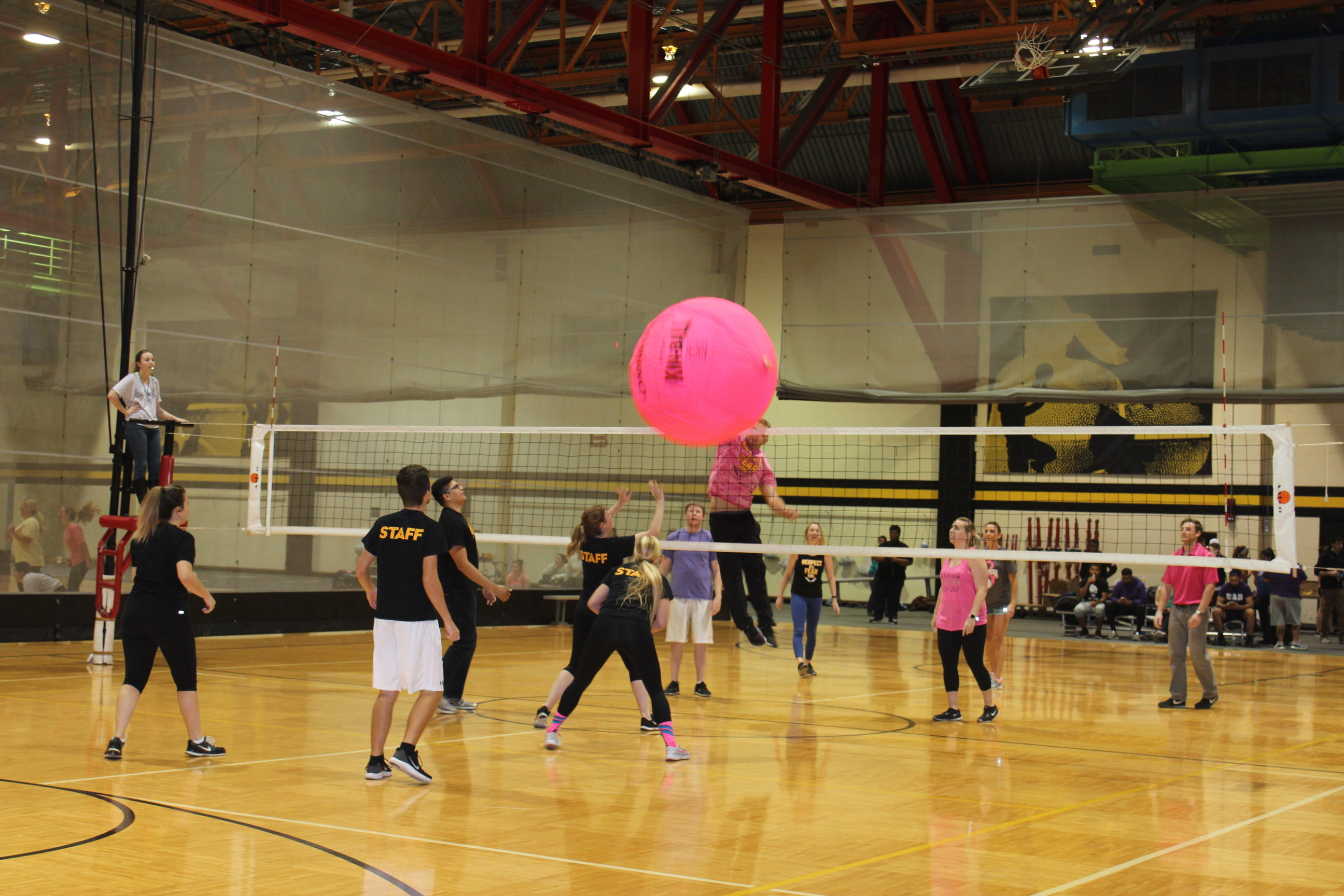 Group of people playing Big Pink Volleyball in the upstairs gym. Referee is on her feet, the ball is in the air between sides.