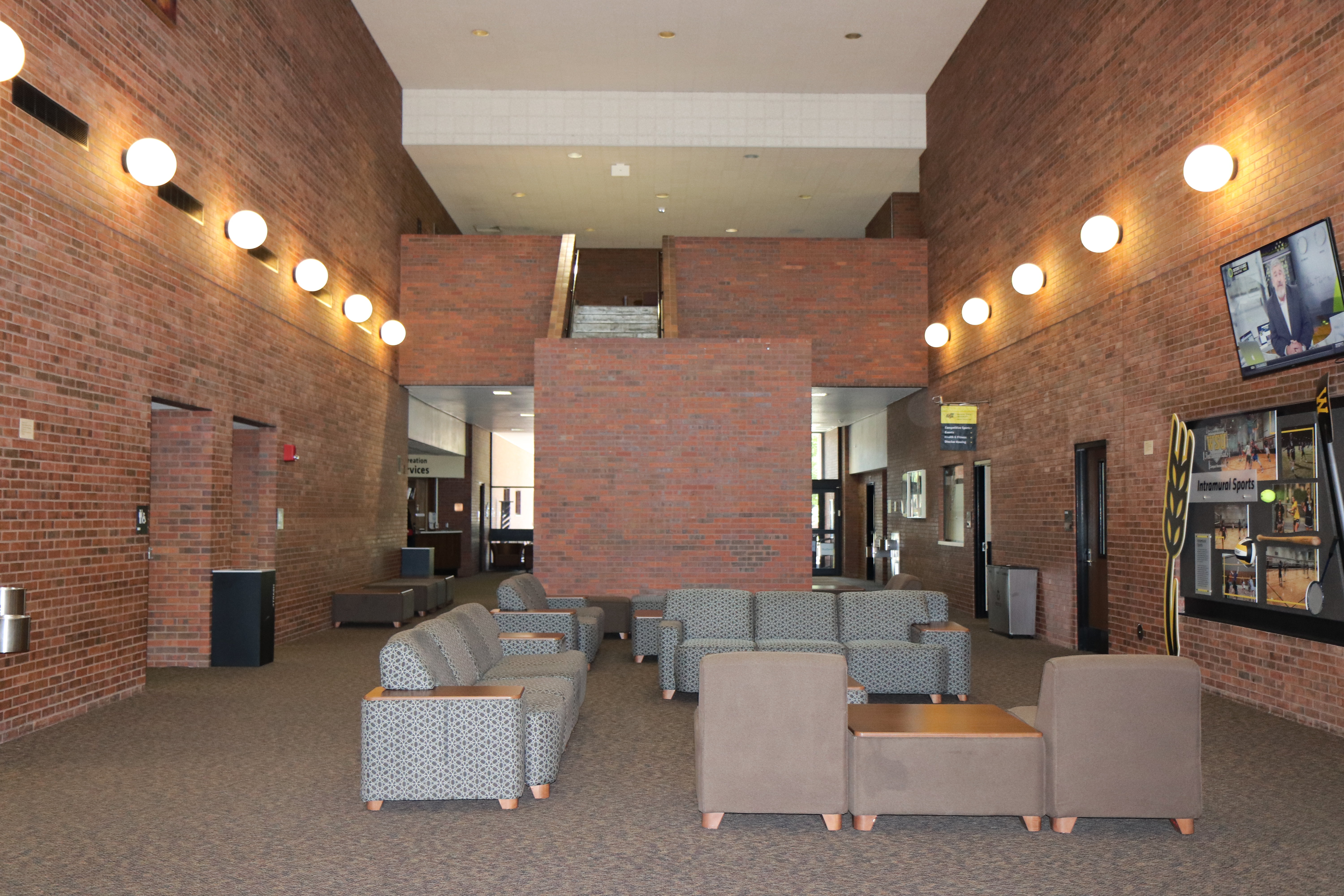 view from the heskett center lobby. seating area with chairs and couches lined by spherical lights on the walls.
