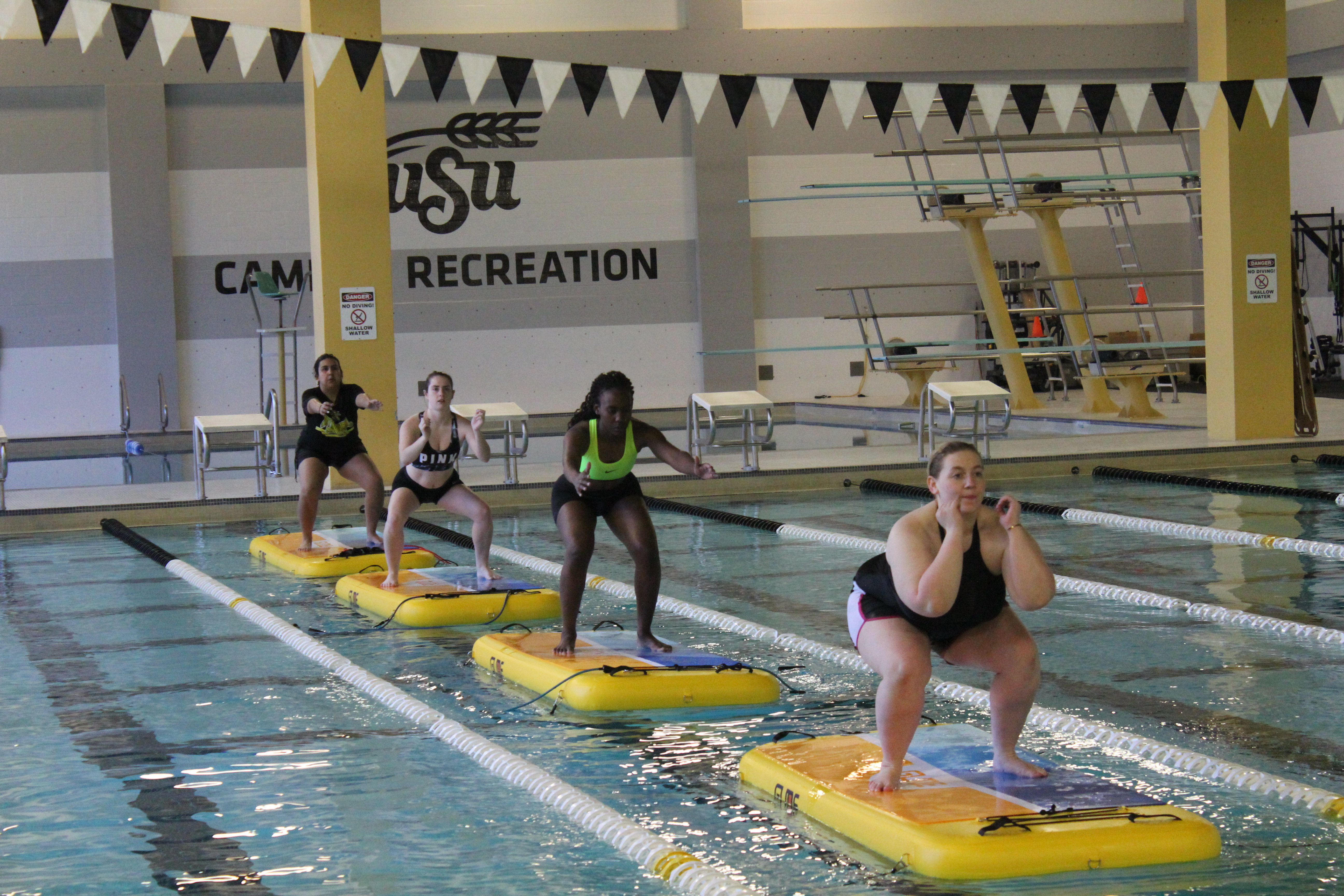 four women standing on glidefit boards in a lane of Wiedemann Natatorium Pool. They are doing a squat.