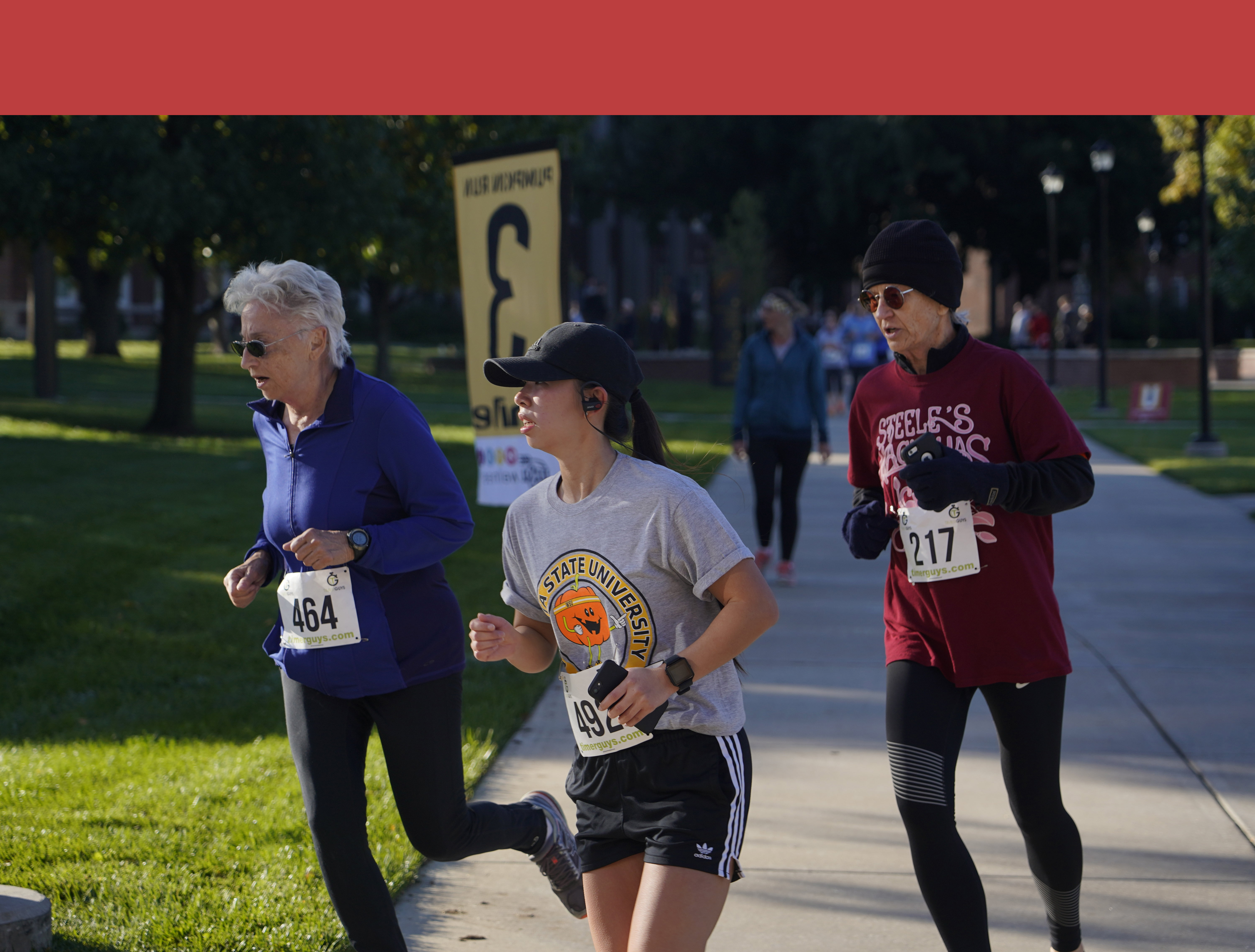 image from the pumpkin run. three runners are in the image, two older people in red and blue and a college student in the pumpkin run shirt in center frame.