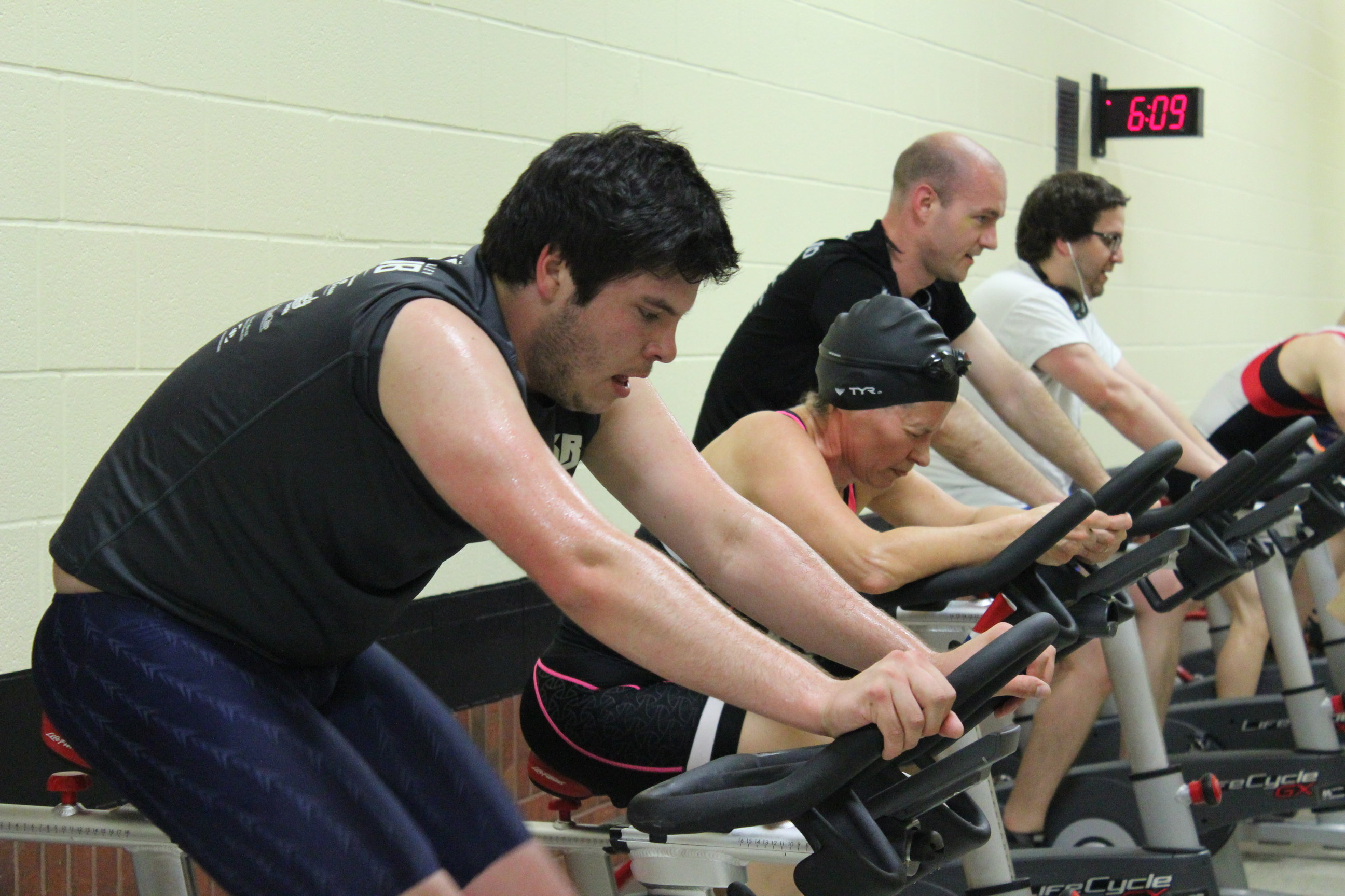 Group of people on stationary bikes. One woman in swim cap and goggles.