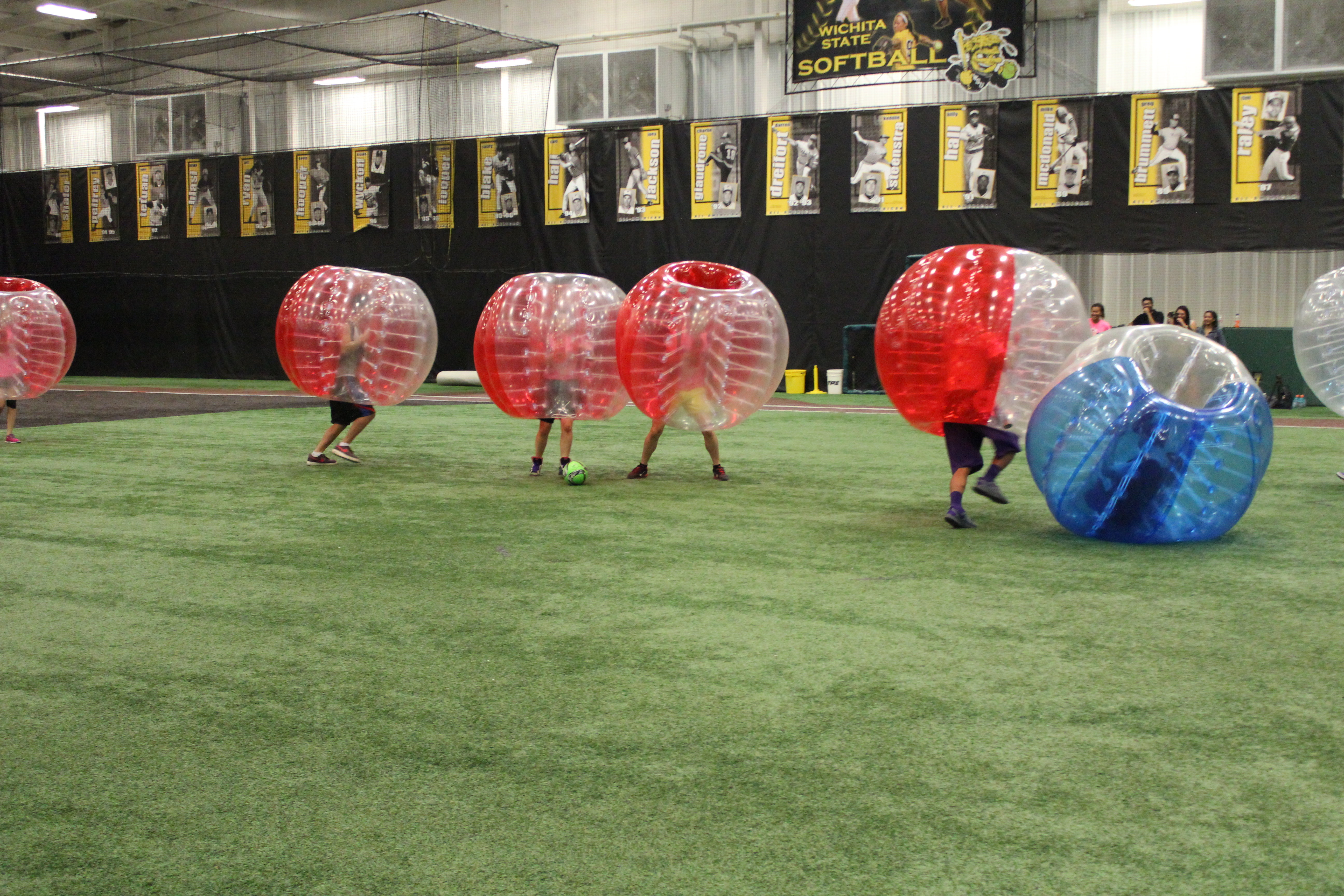 A group playing bubble soccer: people running and playing soccer while their upperbodies are encased in inflatable spheres