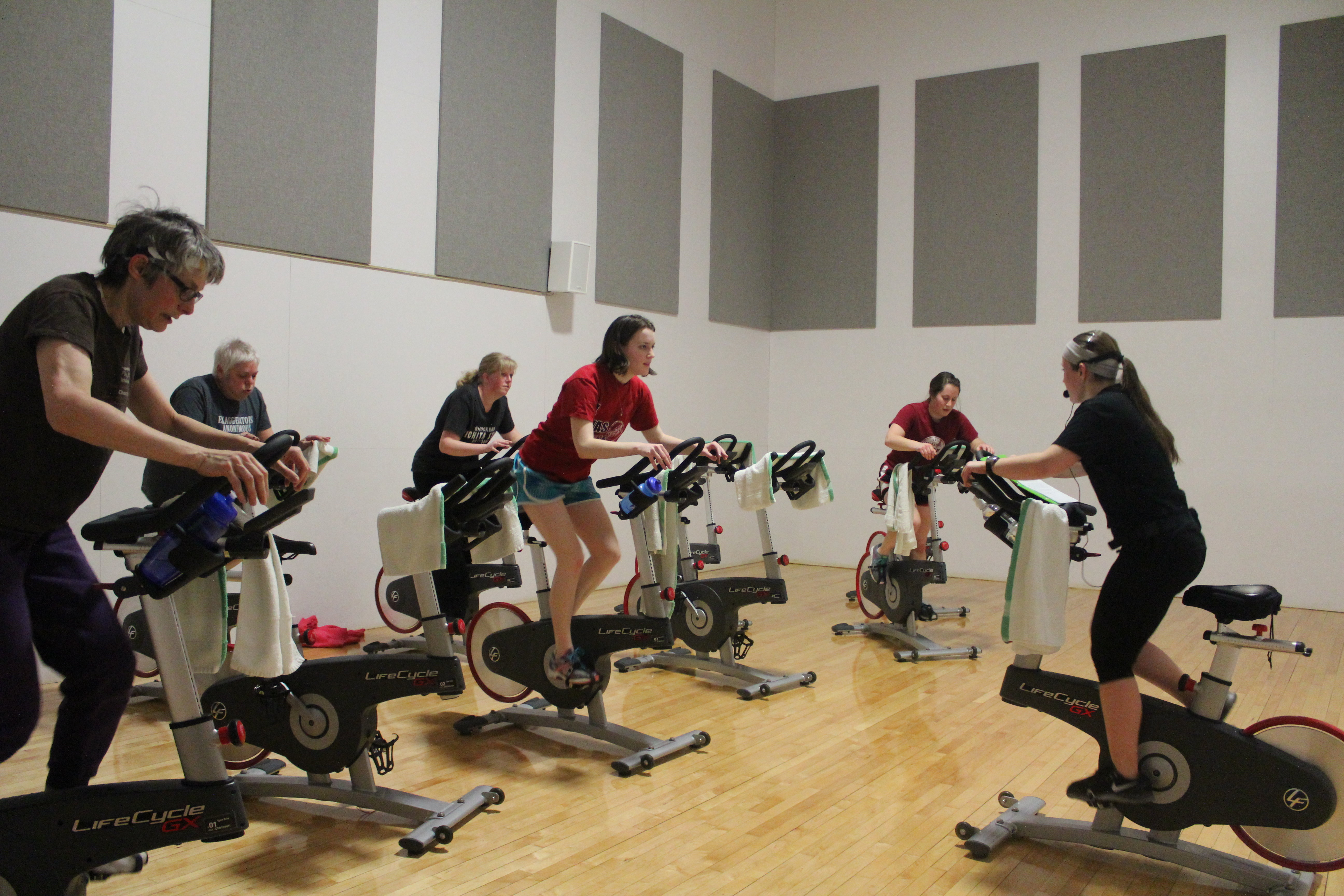 a class of cyclefit. five people on stationary bikes are arranged around an instructor with a headset on.