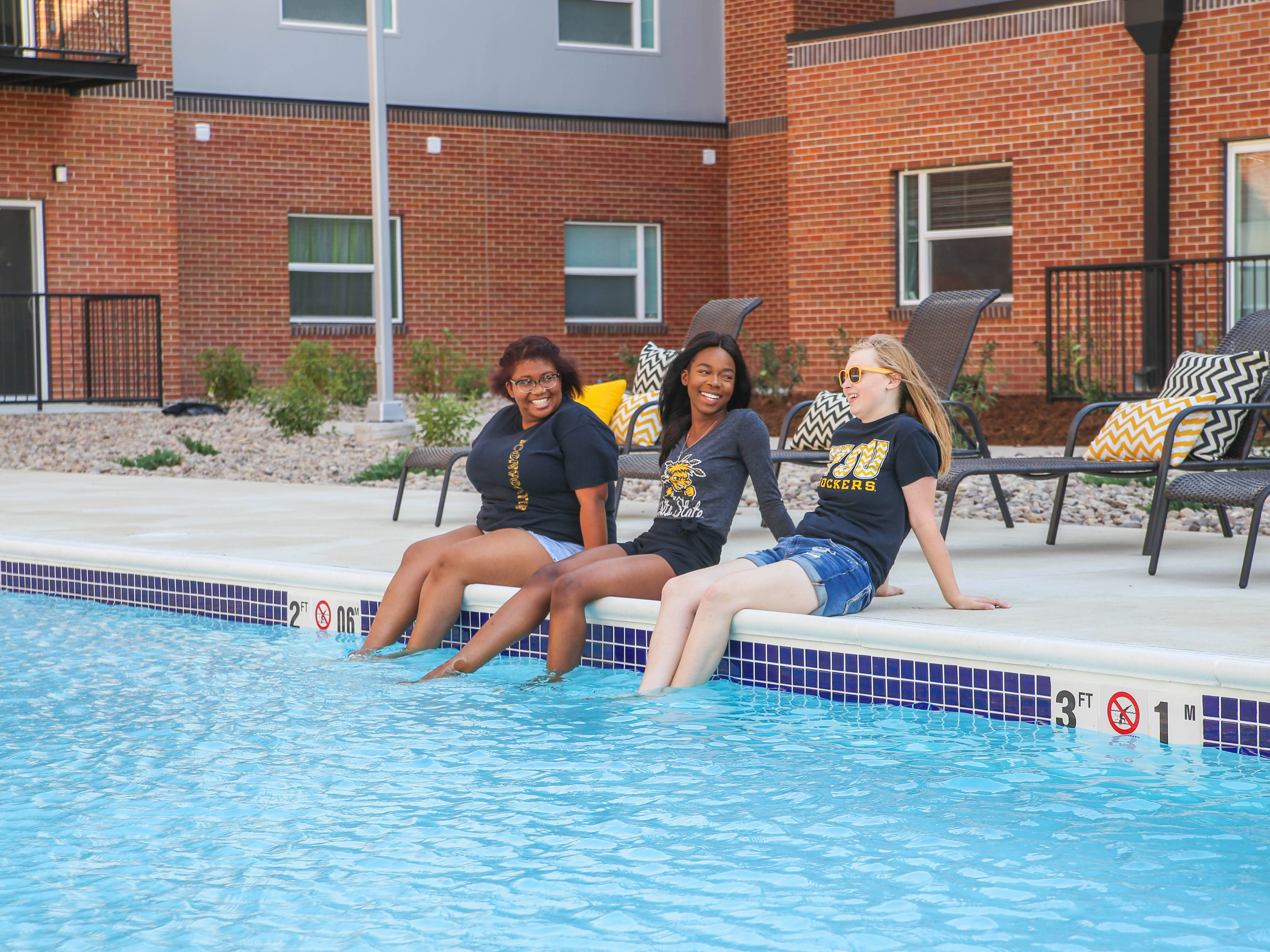 students sitting by pool